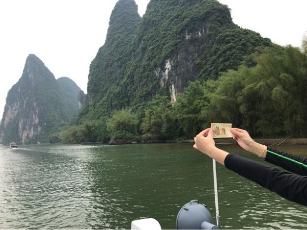 20元のお札を広げて景色と一緒に写真を撮る人。