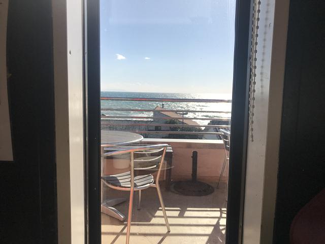 風の強い日はテラスはクローズ。中から見るテラスと海、輝いてる