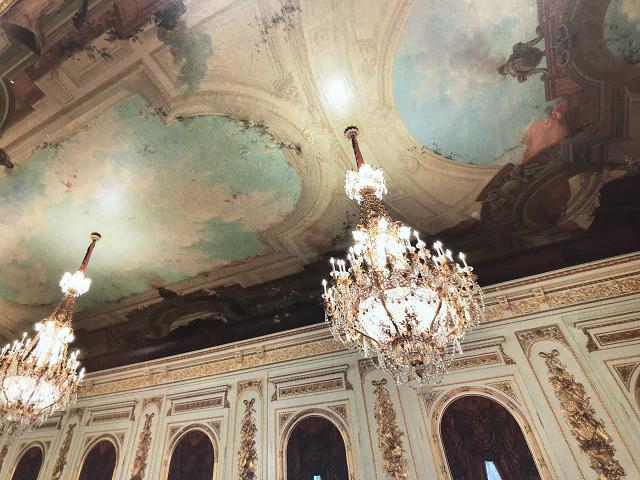 「公式パンフレット 国宝迎賓館 赤坂離宮」より。天井の青い空と楽器などが描かれた壁が印象的。