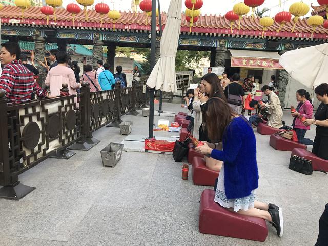 香港の人たち、お寺へのお参りは本当に熱心に行います。おみくじを引くときも膝間づいて、一心不乱に祈ります。